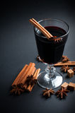 Glass of hot mulled wine. A glass of hot mulled wine, spices, cinnamon, star anise, brown sugar and nuts on a black background in studio Stock Photo