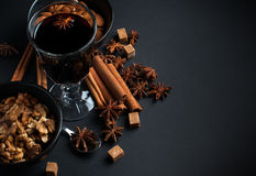 Glass of hot mulled wine. A glass of hot mulled wine, spices, cinnamon, star anise, brown sugar and nuts on a black background in studio Royalty Free Stock Photos