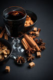 Glass of hot mulled wine. A glass of hot mulled wine, spices, cinnamon, star anise, brown sugar and nuts on a black background in studio Royalty Free Stock Photography