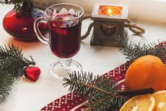 Glass of hot mulled wine on wooden table with candle, orange, cinnamon and christmas tree Royalty Free Stock Image
