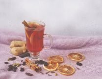 A glass of hot mulled wine and dry ingredients for this on a warm knitwear on a rain window background. royalty free stock photography