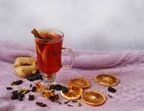 A glass of hot mulled wine and dry ingredients for this on a warm knitwear on a rain window background. stock photography