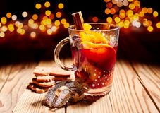 Glass of hot spicy Gluhwein with cookies. On a wooden table with a backdrop of sparkling Christmas party lights Stock Photo