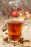 Glass of hot steaming tea among christmas decorations Royalty Free Stock Image