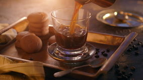 A glass of hot steamy black coffee on a metal tray, standing on a vintage wooden table, surrounded by coffee beans stock footage