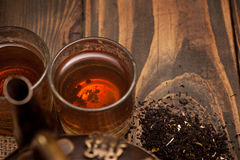 Glass of hot tea and leaves on dark wooden background Stock Image