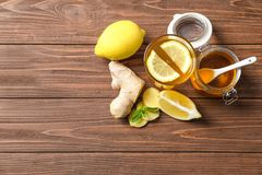 Glass with hot tea, lemon and ginger. As cold remedies on wooden table, top view royalty free stock photos