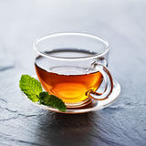 Glass of hot tea with mint garnish. On slate surface stock image