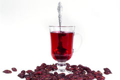 A glass of hot Uzvara of rose hips and berries scattered around. Effective methods to combat colds and flu. Royalty Free Stock Photography