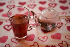 Valentines day drink photography of a glass teapot and cup filled with hot apple spice flavor tea on love heart cloth. A glass of hot warming tea poured from a royalty free stock images