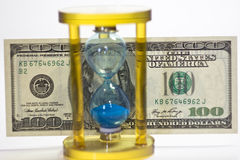 Glass hourglass and money Royalty Free Stock Photo