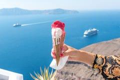 Glass i en dillandekotte i kvinnas hand på bakgrund av den Santorini ön och Caldera i det Aegean havet royaltyfri foto