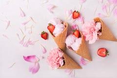 Glass i en dillandekotte på en ljus bakgrund isolerad jordgubbewhite för bakgrund kräm- is Blommor i en dillandekotte Rosa nejlik Arkivfoton