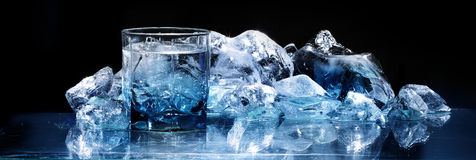 Glass with ice. Glass of water near the ice on the glass Stock Photography