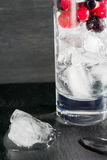 Glass of ice with berry gooseberries red black currants and water. Refreshing cocktail. Summer drink. Royalty Free Stock Image