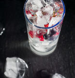 Glass of ice with berry gooseberries red black currants and water. Refreshing cocktail. Summer drink. Stock Photo