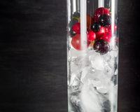 Glass of ice with berry gooseberries red black currants and water. Refreshing cocktail. Summer drink. Royalty Free Stock Photography