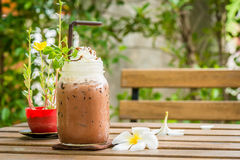 Glass of ice cocoa and plumeria flower put on wooden table Royalty Free Stock Photo