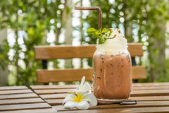 Glass of ice cocoa and plumeria flower put on wooden table Stock Photography