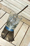 Glass of ice cubes. A clear cold glass of ice cubes with a silver spoon standing on a wooden table outdoors in summer Royalty Free Stock Images