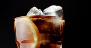 Glass with ice cubes and lemon slide and cola. rom cola, fresh drink, ice cubes and bubbles stock footage