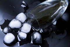 Glass of ice falling on black wet table. Selective focus. Royalty Free Stock Image