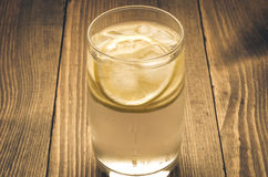 Glass with ice and a lemon on a wooden background. Cocktail with ice and a lemon stock images