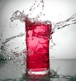 Glass with ice and liquid splash. A glass with ice and liquid splash royalty free stock photos