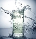 Glass with ice and liquid splash. A glass with ice and liquid splash royalty free stock photo