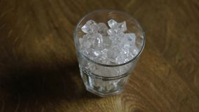 Glass with ice revolves around the axis on the wooden table stock footage