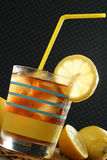 Glass of Ice Tea and Lemons with straw. Glass of ice tea with lemon slice and yellow straw Stock Images