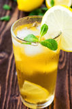 Glass of ice tea with lemons on wooden table Royalty Free Stock Image