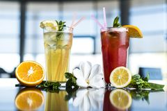 Glass of ice tea with mint and lemon on wooden table royalty free stock photography