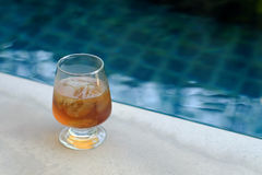 Glass of ice tea beside the pool Royalty Free Stock Photos