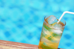 A glass of ice tea at pool with vintage filter background Royalty Free Stock Photography