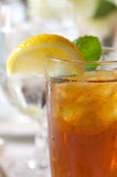 Glass of ice tea on a sun drenched table Royalty Free Stock Images