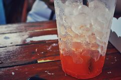 Glass of ice-tea on a wooden table royalty free stock images