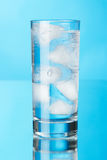 Glass of ice water on blue background Royalty Free Stock Image