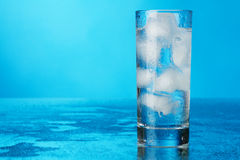 Glass of ice water on blue background Stock Photo