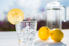 Glass of ice and water decorated with a slice of lemon standing on a white table against a decanter with water and two Royalty Free Stock Photos