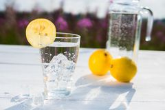 Glass of ice and water decorated with a slice of lemon standing on a white table against a decanter with water and two Stock Images
