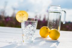 Glass of ice and water decorated with a slice of lemon standing on a white table against a decanter with water and two Stock Photos