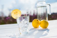 Glass of ice and water decorated with a slice of lemon standing on a white table against a decanter with water and two Royalty Free Stock Image