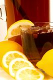 Glass of iced tea. Close up of a glass of iced tea with lemons arranged around it and a pitcher in the back Stock Photos