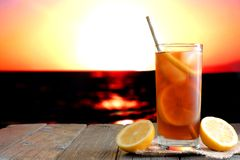 Glass of iced tea against a vibrant ocean sunset background. Glass of iced tea with straw on wood against a vibrant ocean sunset background Royalty Free Stock Images