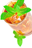 Glass of iced tea with mint. Glass of iced tea with ice cubes and mint on white background stock photo