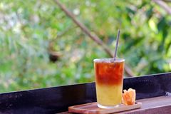 A glass of iced tea soft drink in a wooden tray with an orange flower on wood balcony. Green nature background royalty free stock photo