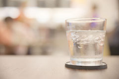 Glass of iced water. On top of wooden table with unrecognizable blurry people in restaurant background stock photography