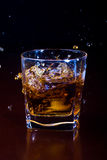 Glass of iced whiskey. A glass of iced whiskey on a brown table in the dark stock image