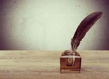 Feather quill pen and glass inkwell on library. Glass ink pen feather well inkwell quill Royalty Free Stock Photos